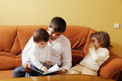 Dad reading book to daughters Royalty Free Stock Photo