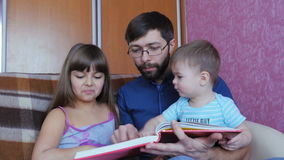 Dad Reading a Children`s Book To His Children stock video