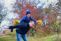 Dad rolls his son on his back in the autumn park Stock Image