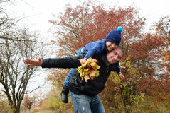 Dad rolls his son on his back in the autumn park Royalty Free Stock Photography