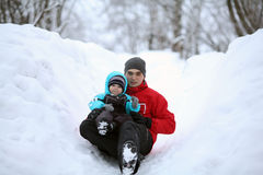 Dad rolls with ice slide with a his son Stock Images