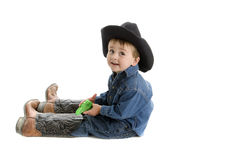 Dad's boot are hard to fill. Little cowboy sits on floor with his dad's boots on with squirt gun in hand Stock Photo