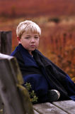 Dad's Coat 2. A young boy sits on a bench with his Dad's coat to keep him warm Royalty Free Stock Image