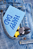 Dad`s Day fabric greeting card. Pliers and card on jeans. Send best wishes to father Stock Images