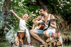 Dad plays the guitar, daughter on the nature. Dad`s family camping plays guitar to his daughter in nature, the concept of family values and pastime royalty free stock photo