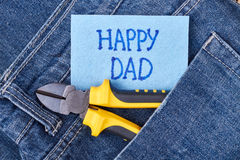Dad`s greeting paper and jeans. Pliers on pocket near card. How to congratulate father Stock Photography