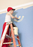 Dad's Helper. Young boy standing on a ladder helping his dad paint Royalty Free Stock Images