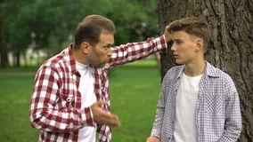 Dad scolding his son for bad behavior, education process, fathers and children. Stock footage stock footage