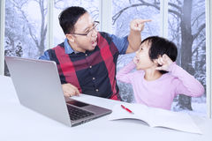 Dad screaming on his child to study. Portrait of young father giving order on his daughter to study and doing homework at home Royalty Free Stock Image