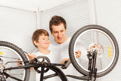 Dad showing his kid son how to repair bicycle Royalty Free Stock Photo