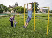 Dad shows exercises on the bar for his son. Stock Photo