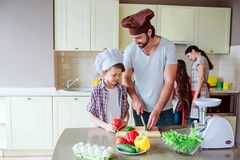 Dad shows his son how to cut vegetables right. Gir works with her mom behind boy close to stowe. Family is preparing. Breakfast together Royalty Free Stock Images