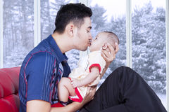 Dad sitting on sofa and kiss his baby. Portrait of happy dad sitting on sofa while holding and kissing his little son, shot with winter background on the window royalty free stock photography