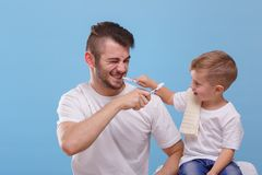 Dad with a small son, having fun together, brushing each other`s teeth. On a blue background. Young dad with a small son, dressed in white T-shirts, having fun Royalty Free Stock Images