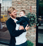 Dad with a small son in his arms. Against the wall on the street stock photo