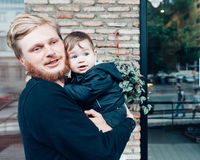 Dad with a small son in his arms. Against the wall on the street stock images