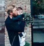Dad with a small son in his arms. Against the wall on the street royalty free stock image