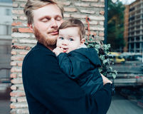 Dad with a small son in his arms. Against the wall on the street royalty free stock photos