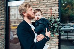 Dad with a small son in his arms. Against the wall on the street stock image