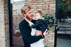 Dad with a small son in his arms. Against the wall on the street stock photos