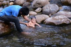 Dad and smiling boy swimming in the river stock images