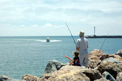 Dad and son 1 fishing at beach Royalty Free Stock Images