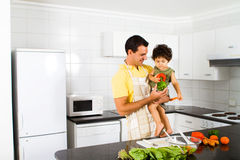 Dad and son. Happy dad holding toddler son in a modern kitchen stock images