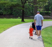 Dad and son. Young dad with a hat on walking with toddler son in park setting royalty free stock photos