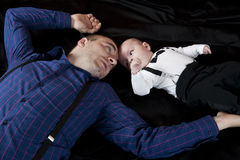 Dad and son. Portrait with dad and little son laying on black background Royalty Free Stock Images