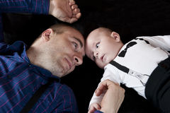 Dad and son. Portrait with dad and little son laying on black background Royalty Free Stock Photos