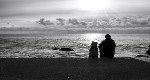 Dad and son along the seashores, backlight. Black and white photo. Genova, Italy - January 3, 2016: silhouette of a man and his son, sitting in front of the Stock Image