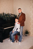 Dad and son around piano with Christmas Stock Photos