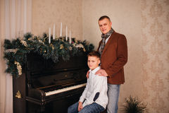 Dad and son around piano with Christmas Royalty Free Stock Image