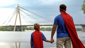 Dad and son as supermen team looking at city, motivated for successful future stock photos