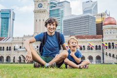 Dad and son on background of Merdeka square and Sultan Abdul Samad Building. Traveling with children concept.  stock photos