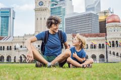 Dad and son on background of Merdeka square and Sultan Abdul Samad Building. Traveling with children concept.  royalty free stock photography