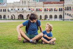 Dad and son on background of Merdeka square and Sultan Abdul Samad Building. Traveling with children concept.  stock images