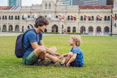 Dad and son on background of Merdeka square and Sultan Abdul Samad Building. Traveling with children concept.  royalty free stock image