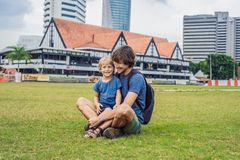 Dad and son on background of Merdeka square and Sultan Abdul Samad Building. Traveling with children concept.  stock photo
