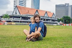 Dad and son on background of Merdeka square and Sultan Abdul Samad Building. Traveling with children concept.  stock image