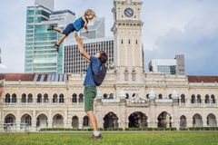 Dad and son on background of Merdeka square and Sultan Abdul Samad Building. Traveling with children concept.  stock photography