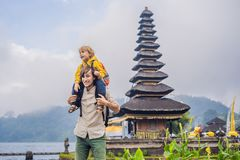 Dad and son in the background of Pura Ulun Danu Bratan, Bali. Hindu temple surrounded by flowers on Bratan lake, Bali. Major Shivaite water temple in Bali stock photos