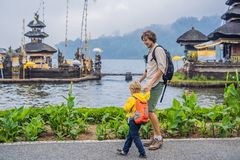 Dad and son in the background of Pura Ulun Danu Bratan, Bali. Hindu temple surrounded by flowers on Bratan lake, Bali. Major Shivaite water temple in Bali royalty free stock photo