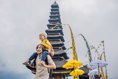 Dad and son in the background of Pura Ulun Danu Bratan, Bali. Hindu temple surrounded by flowers on Bratan lake, Bali. Major Shivaite water temple in Bali stock image
