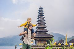 Dad and son in the background of Pura Ulun Danu Bratan, Bali. Hindu temple surrounded by flowers on Bratan lake, Bali. Major Shivaite water temple in Bali stock photography