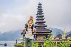 Dad and son in the background of Pura Ulun Danu Bratan, Bali. Hindu temple surrounded by flowers on Bratan lake, Bali. Major Shivaite water temple in Bali stock images