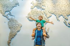 Dad and son on the background of a world map with an airplane in his hands. Travel concept stock photography