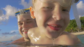 Dad and son bathing in the sea stock footage