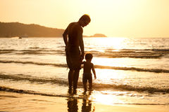 Dad and son on the beach. Dad and son walking along the beach during the sunset Stock Photo