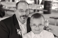 Dad and Son in Black and White. Father and young son on wedding day. They both wear glasses. This shot is in black and white Stock Photos